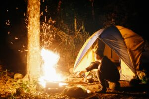 man keeping his tent warm